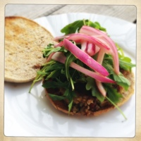Roasted Strawberry and Kale Quinoa Burger topped with Arugula, Pickled Onions and Goat Cheese